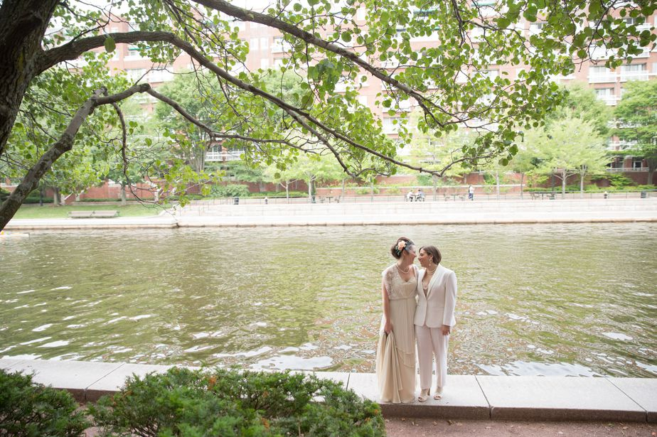 two brides walk along the charles at cambridge multicultural center wedding