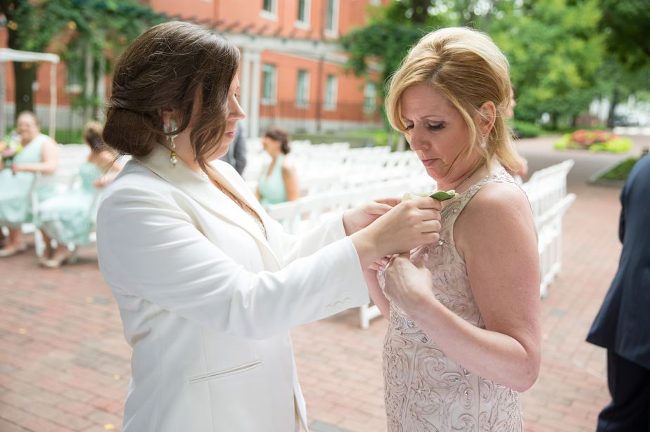 bride puts flowers on mom at gay wedding cambridge multicultural center wedding