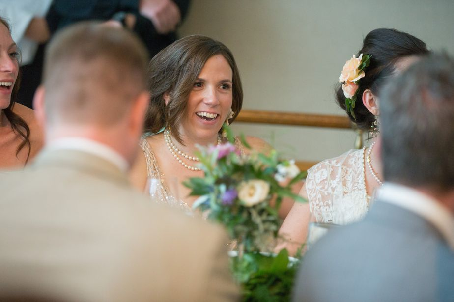 cute bride laughs at toasts at CMAC wedding