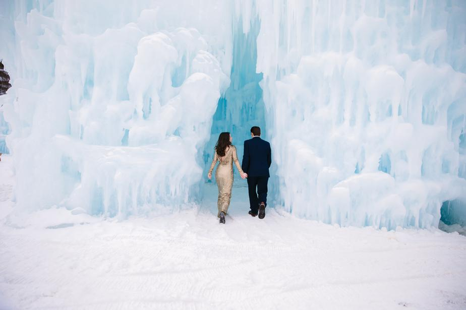 bride and groom walk into the ice castles in NH