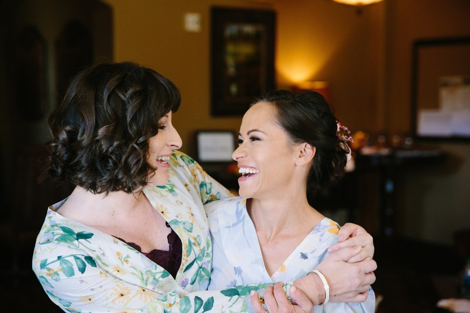 bride and bridesmaid laugh during prep in flower robes