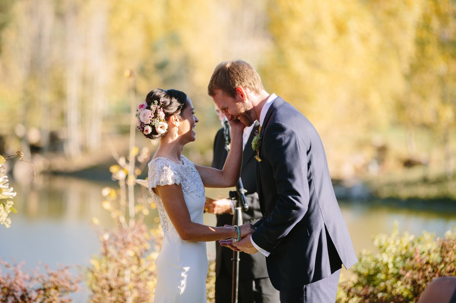 bride laughs flowers in hair and BHLDN dress on