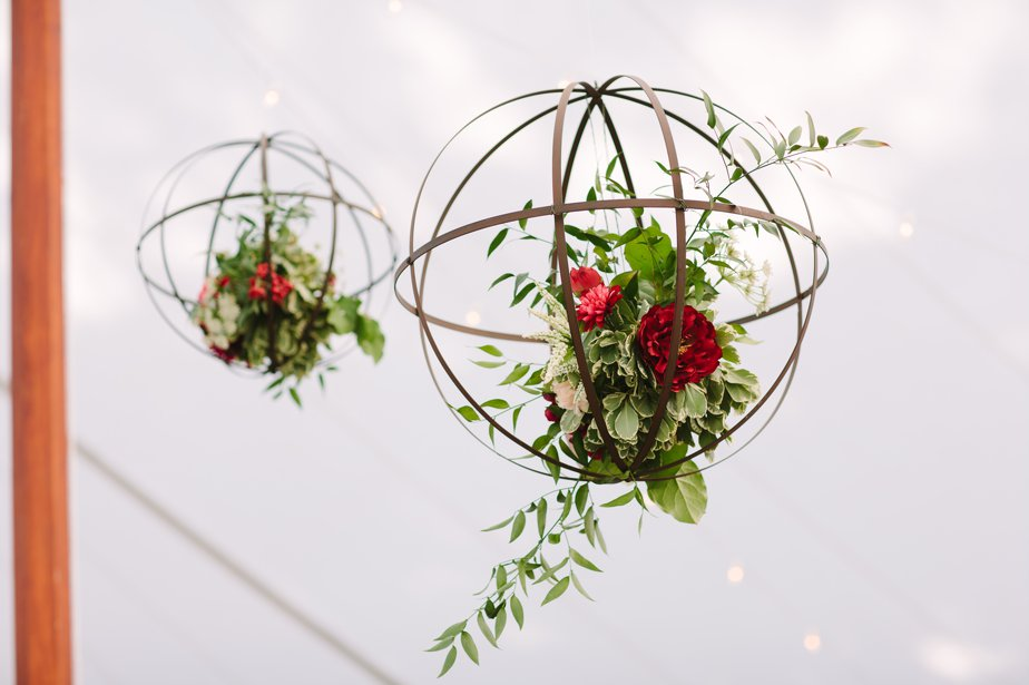 florals hung in orbs on ceiling of tent at morain farm wedding