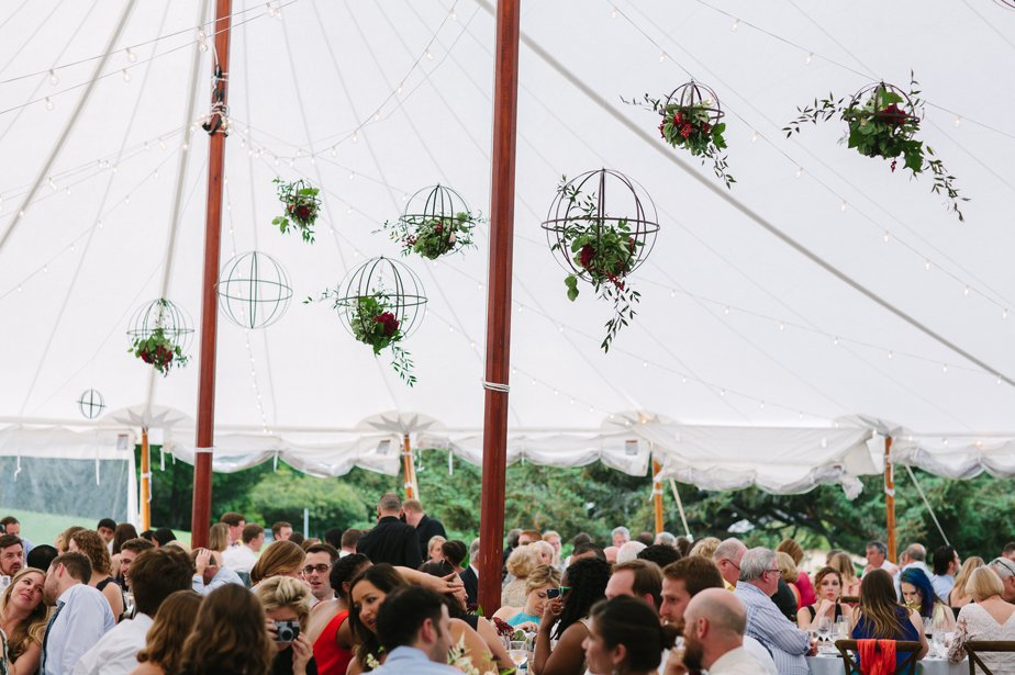 hanging orbs of flowers in tent at moraine farm wedding