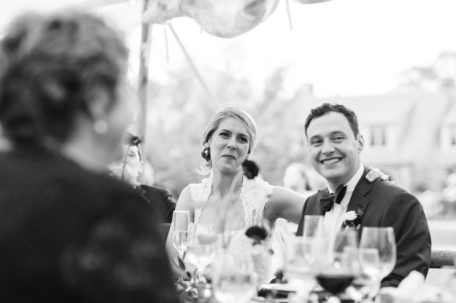 bride and groom smile during toasts at moraine farm