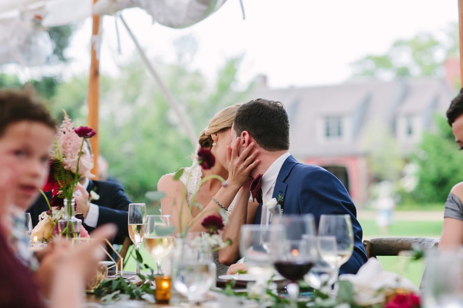 couple kissing during toasts at moraine farm wedding