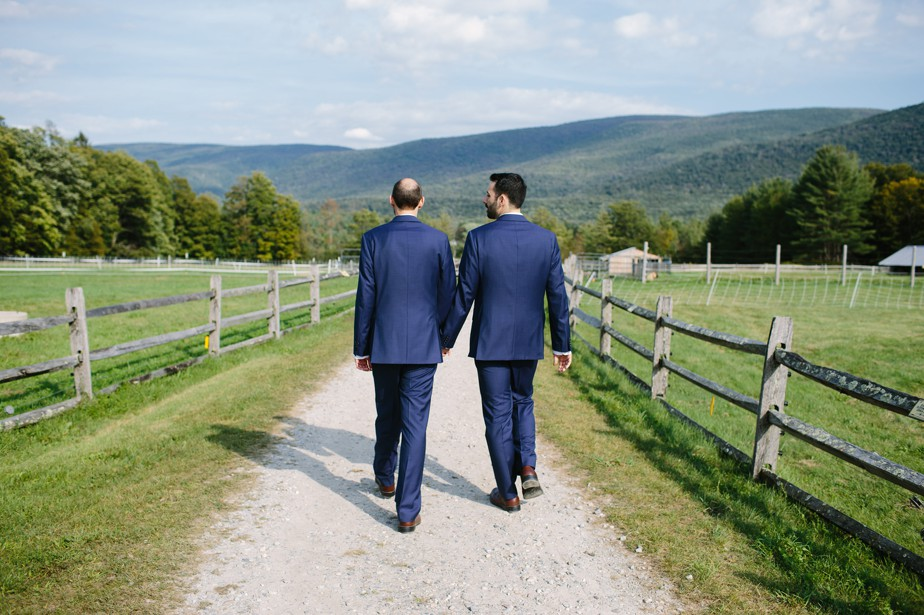 two grooms walk on a goat farm at hildene wedding vermont