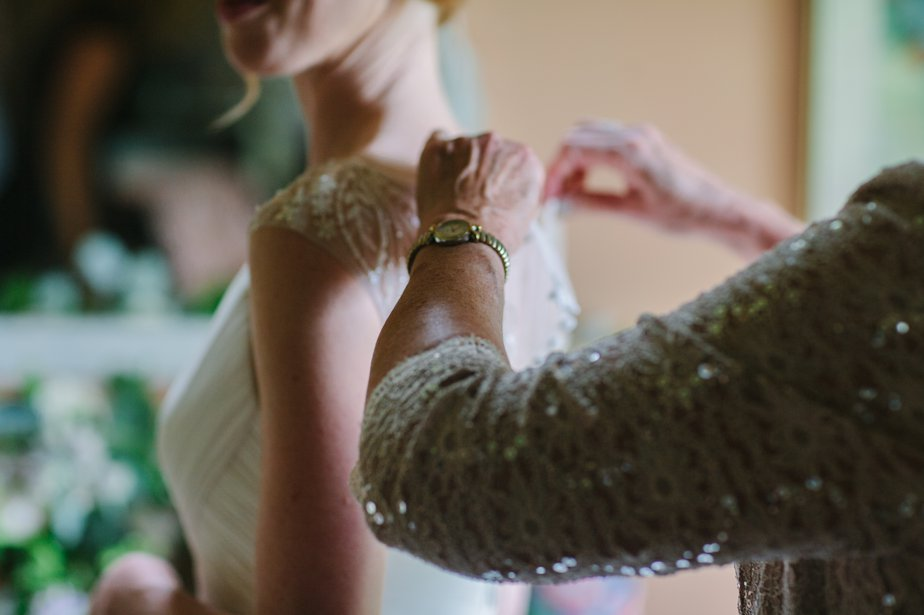mom helps bride put dress on in oregon