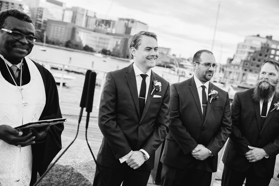 grooms first look at bride at ceremony on boston harbor