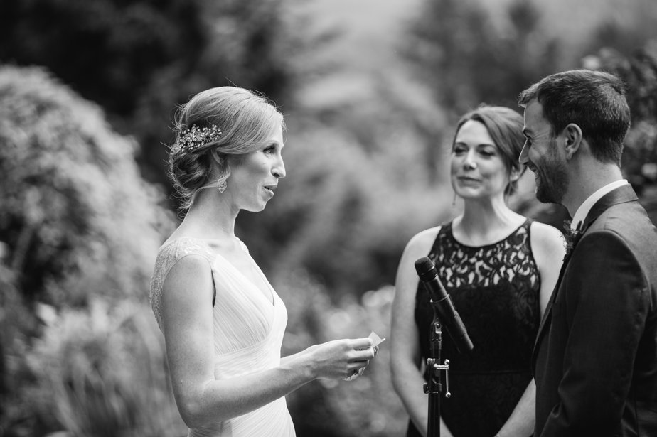 bride reads vows in outdoor ceremony in a garden wedding