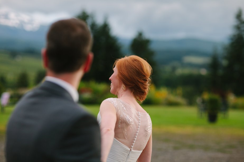 bride holds hand infront of mountain