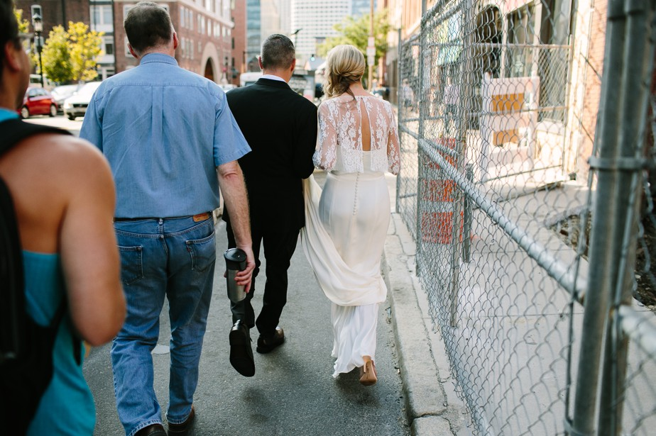 couple walks through downtown boston on their wedding day