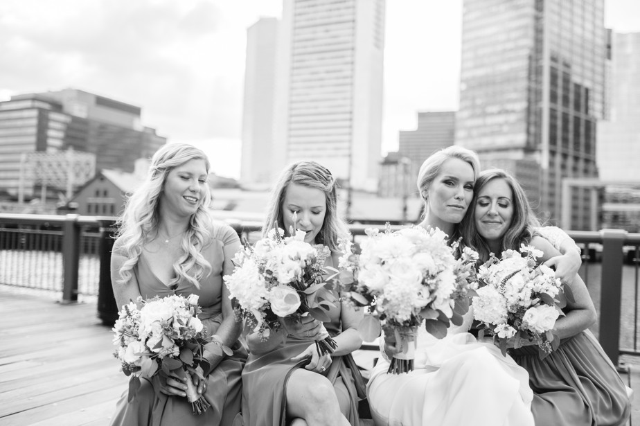 bride hugs bridesmaid boston harbor