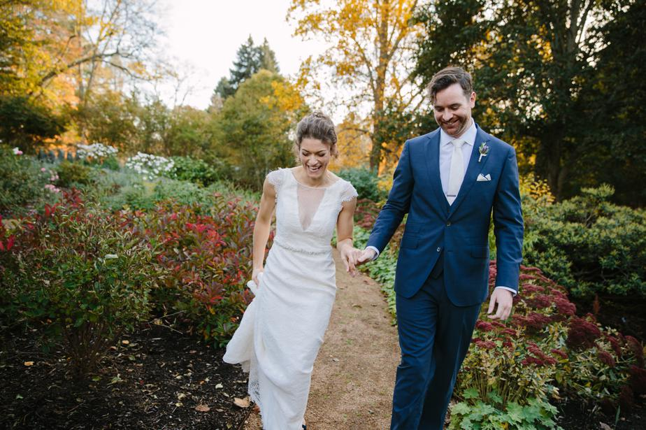 couple walks through garden at the estate at moraine farm wedding