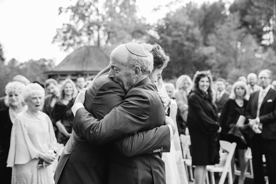 hugs in the aisle at the estate at moraine farm wedding