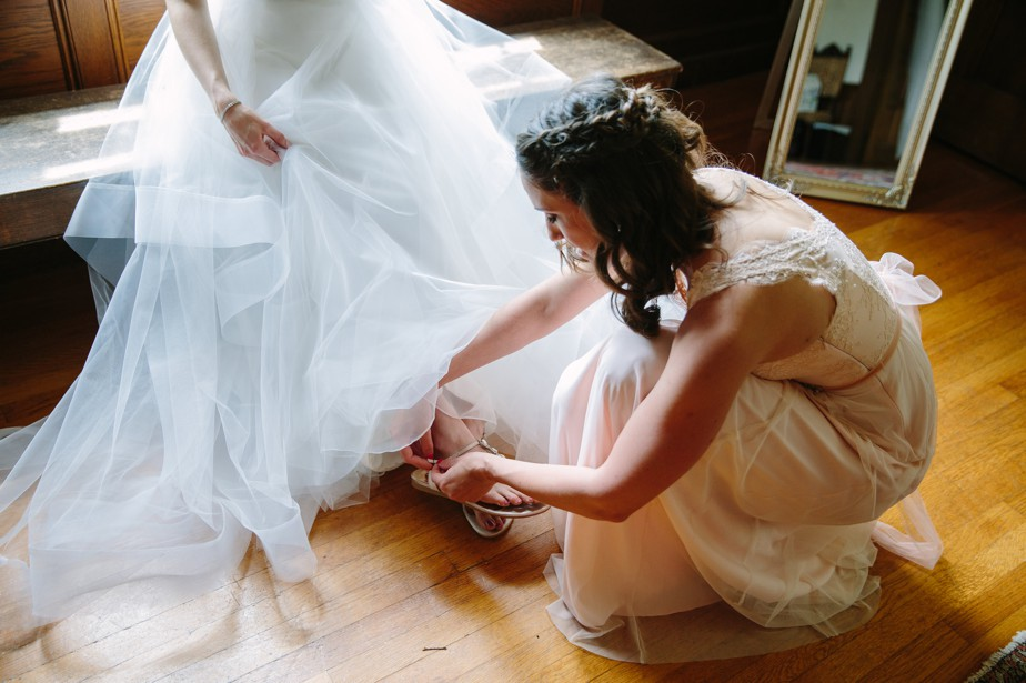 maid of honor helps with wedding sandals at waterworks museum wedding in Brookline, MA