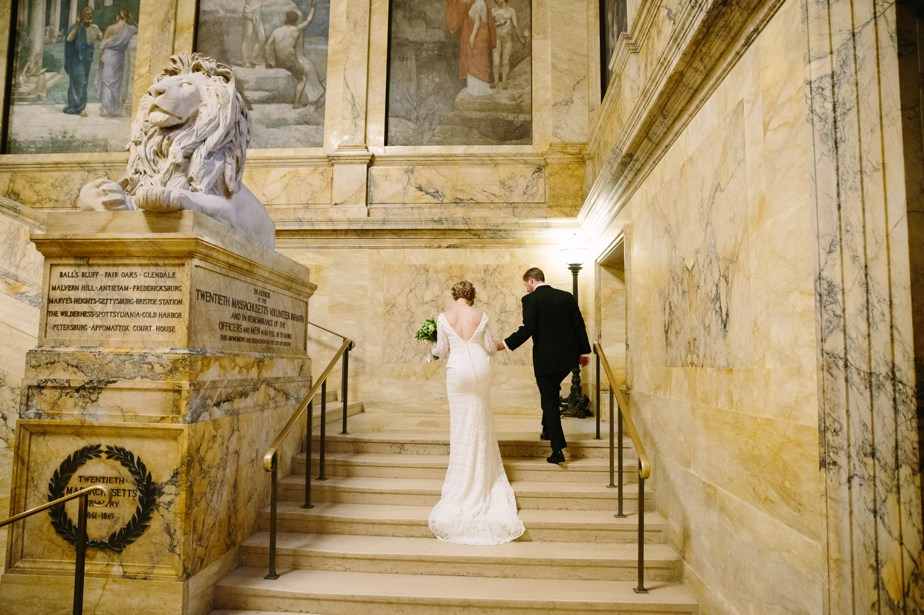 couple climbs grand staircase at boston public library wedding